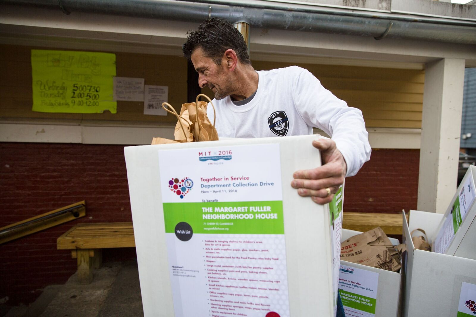 A volunteer distributing food donations to the Margaret Fuller House food pantry in 2016