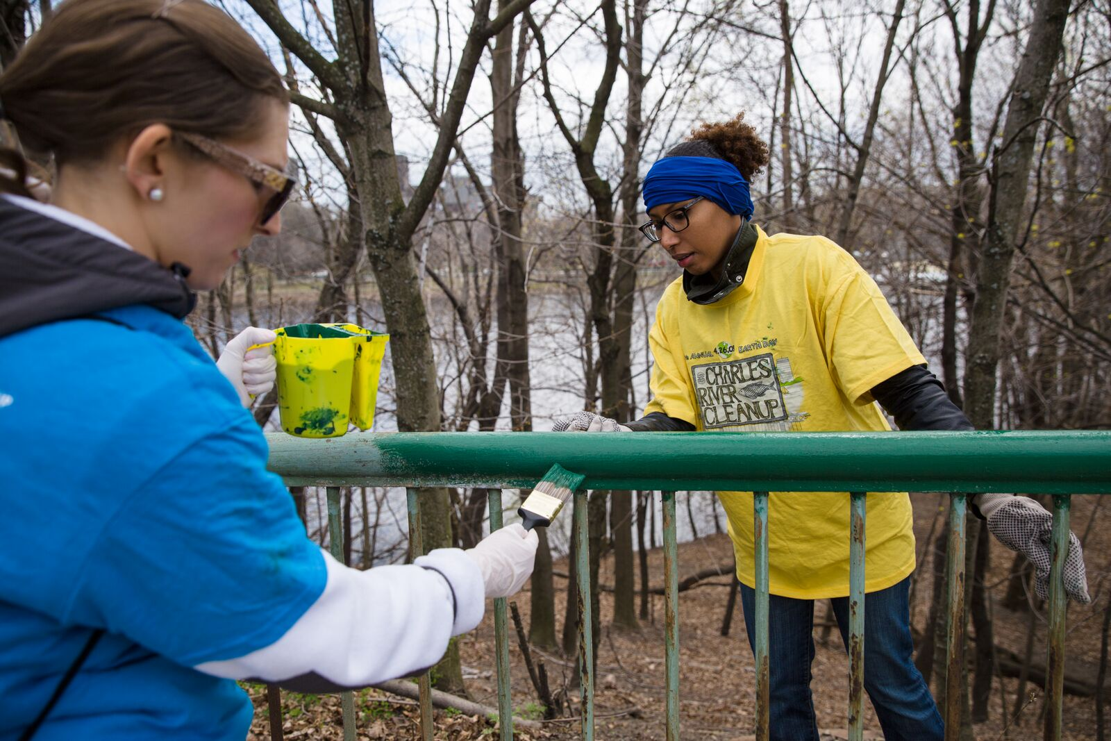 Volunteers painting a railing along the Charles River with the Charles River Cleanup crew