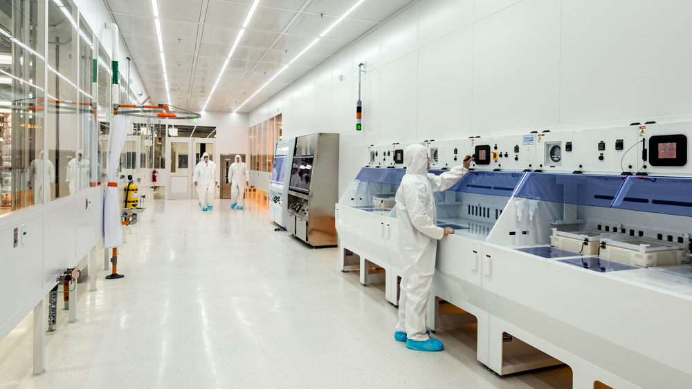 a photograph of suited lab works in a clean lab at MIT Nano
