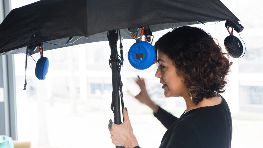 woman standing under an umbrella at the AI and arts event