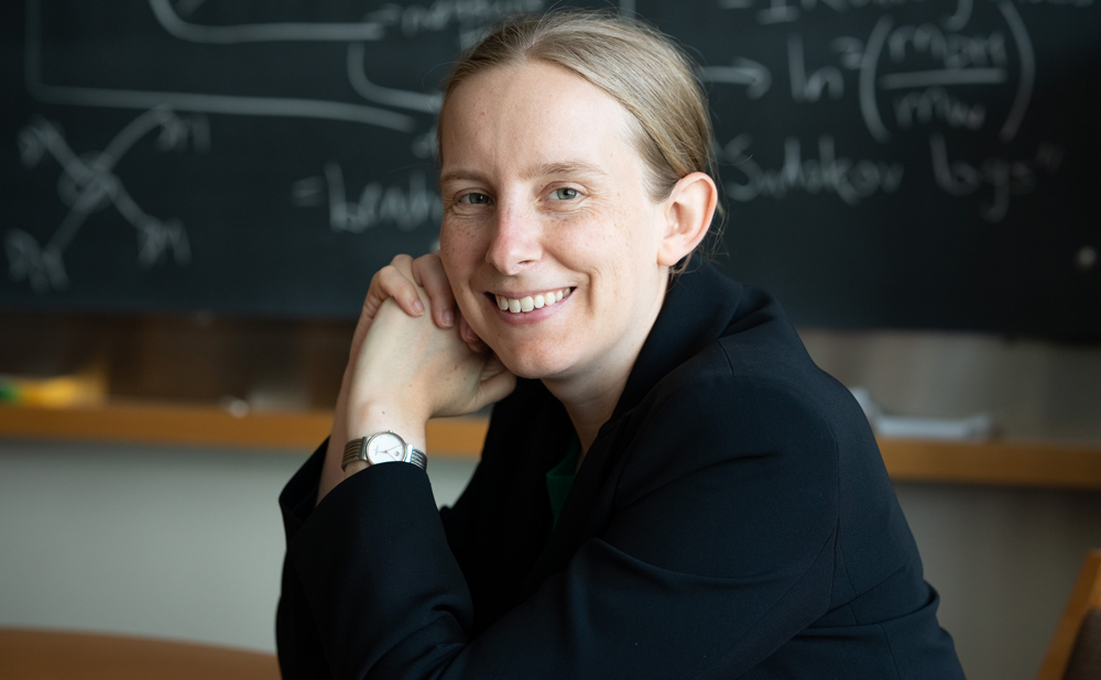 Tracy Slatyer sitting in front of a blackboard covered in mathematical equations