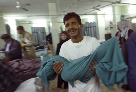 Iraqi man Ahmed Kadim carries his five-year-old dead nephew Rida Serhan out of the emergency room of Baghdad