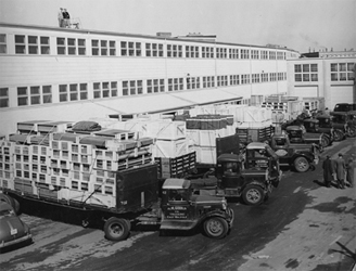 Trucks line up to deliver materials and remove radar sets at MIT's Building 20, home base for the Rad Lab.