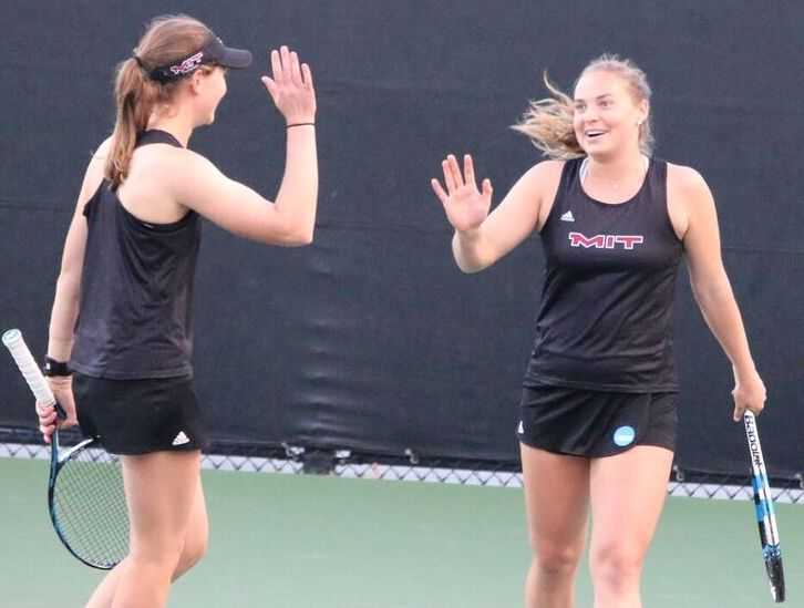 Players on the women's tennis team celebrate a win.